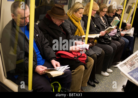 People sitting and reading on a London Tube. - Stock Photo