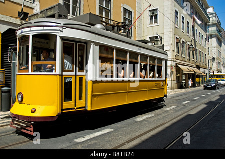 A brightly painted tram carrying a full load of passengers to Prazeres, Lisbon - Stock Photo