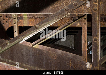 Metal triangles pattern of old bridge beams supporting deck. - Stock Photo