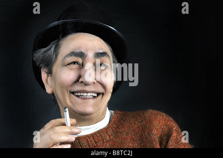 Portrait on black backround of artistic mature smiling woman with hat and cigarette in her hand - Stock Photo