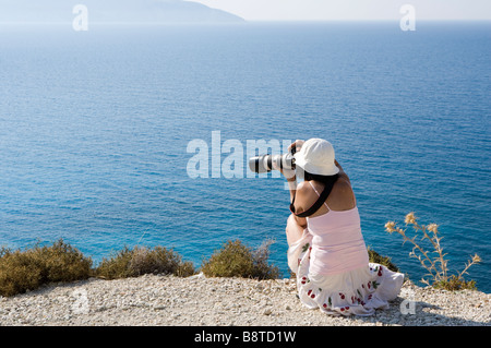 Lady photographer at Mirtos beach, Kefalonia, Greece, Europe - Stock Photo