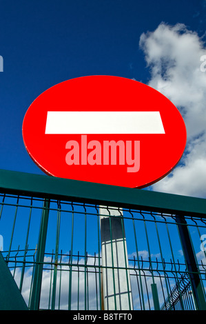Concept  Red No Entry sign and blue sky at secure metal fenced facility - Stock Photo