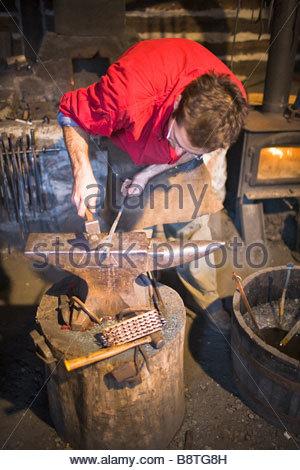 Blacksmith hammering on an anvil.  Festival du Voyageur, Winnipeg, Manitoba, Canada. - Stock Photo