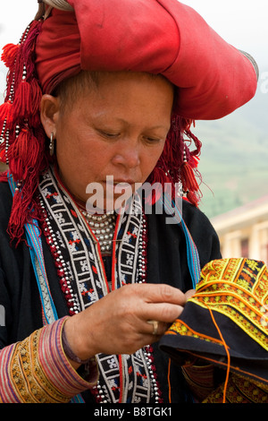 Colourful Dao mountain lady of northern Vietnam partaking in a spot of embroidery - Stock Photo