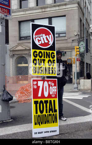 A worker holds up a sign advertising that the Circuit City electronics store is liquidating in New York - Stock Photo