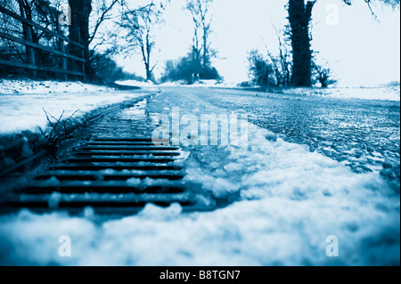 A roadside drain with melting snow - Stock Photo
