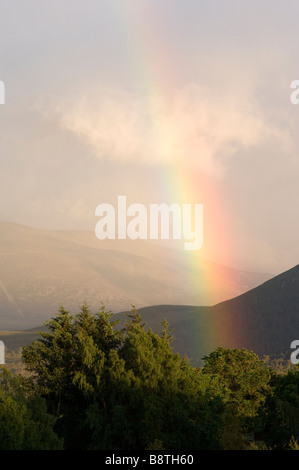 Rainbow over the Lairig Ghru pass viewed across Rothiemurchus Forest in the Cairngorms, Scotland. - Stock Photo