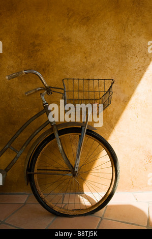 Old bicycle leans against a rustic wall in the shade - Stock Photo