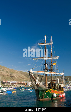 The 'Jolly Roger' pirate party tour boat flying the Spanish flag in Los Cristianos harbour Tenerife Canary Islands - Stock Photo
