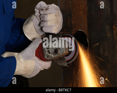 Hands with protective gloves using angle grinder on iron sparks heat friction - Stock Photo