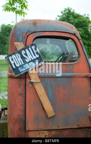 Old truck with a for sale sign stuck in the handle - Stock Photo