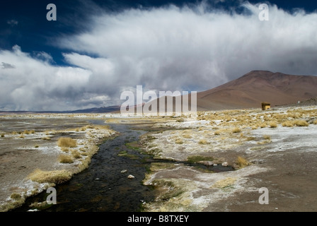 Striking clouds swirl above the hills surrounding the thermal pools of Termas de Polques high on the Bolivian Altiplano. - Stock Photo