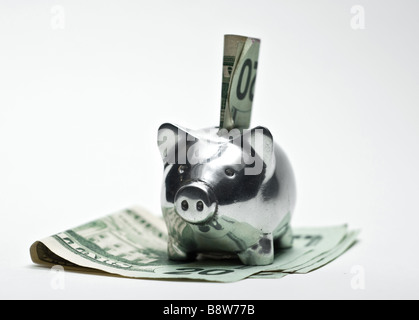 A silver piggy bank with a twenty dollar bill being stuffed into it - Stock Photo