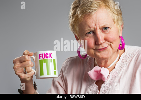 Middle aged woman with grumpy expression holding mug with expletive - Stock Photo