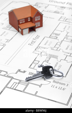 A model home and house key on architectural floor plans - Stock Photo