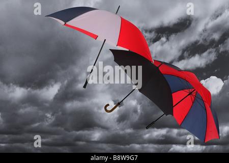Three umbrellas being blown across a dark stormy cloudy sky - Stock Photo