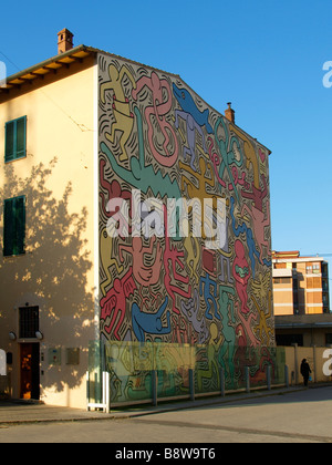 Large colorful mural by world famous US graffiti artist Keith Haring on the side of a building in Pisa Tuscany Italy - Stock Photo