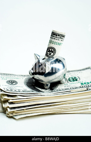 A silver piggy bank with a hundred dollar bill being stuffed into it over a stack of cash. - Stock Photo