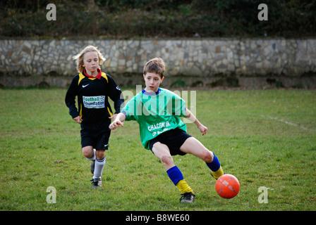 young boys playing football, uk - Stock Photo