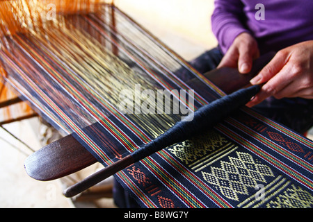 Asian People. Close up of hands of a Vietnamese woman weaving with a spindle a colourful silk scarf in Dalat. Vietnam - Stock Photo