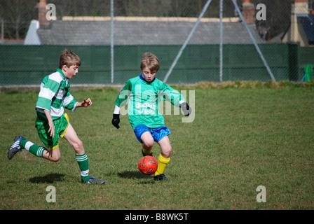 young boys playing football. uk - Stock Photo