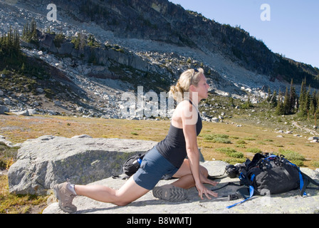 Young woman in mountains doing yoga - Stock Photo