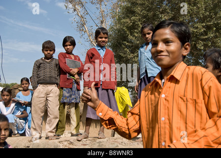 Children gathered around the site of a new water pump in their traditional Indian village. - Stock Photo