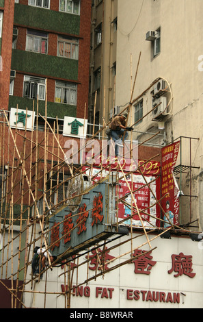 Workers constructing bamboo scaffolding around sign Hong Kong  April 2008 - Stock Photo