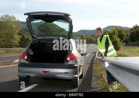Woman standing behind the armco barrier with her broken down car waiting for help on a motorway slip road - Stock Photo