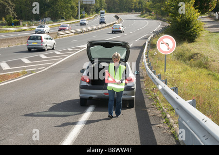 Woman placing her red warning triangle sign behind her broken down car on a slip road onto a French autoroute - Stock Photo