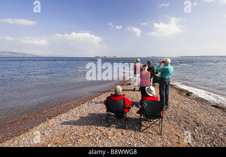 People dolphin-watching from Chanonry Point on the Moray Firth, Scotland. - Stock Photo