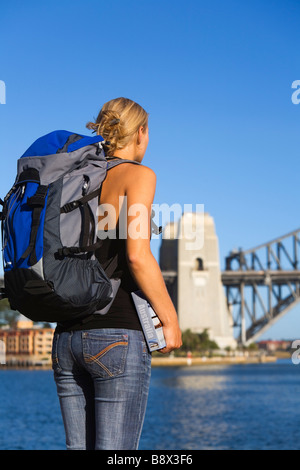 A young backpacker with guidebook on Sydney harbour.  Sydney, New South Wales, AUSTRALIA - Stock Photo