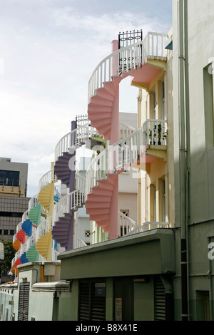 The spiral back staircases of restored Singapore shophouses, here painted in rainbow colours - Stock Photo