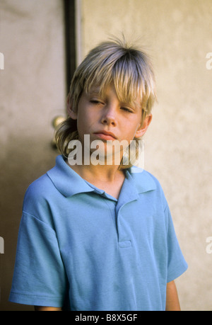 boy mad angry pout blond long hair sad worry worried concern upset blue unhappy depressed - Stock Photo