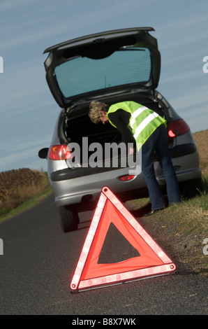 Woman with her broken down car parked at the roadside wearing yellow high visibility / hi viz jacket and warning - Stock Photo