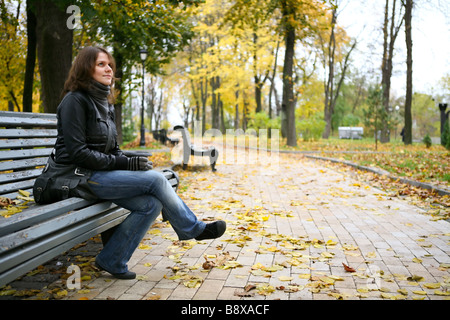 Female sitting on a bench in park - Stock Photo