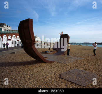 Teenagers playing on a modern art sculpture called Passacaglia. Brighton Beach, Sussex, England, UK.