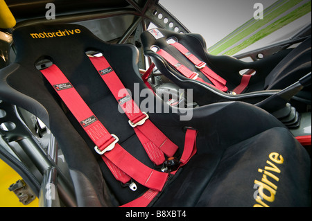 car interior showing bucket seats and racing seat belts - Stock Photo