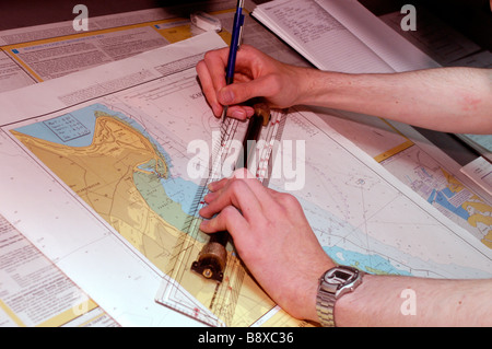 An officer of the Royal Fleet Auxiliary plots the ship s position on a nautical chart on the bridge of the RFA Wave - Stock Photo