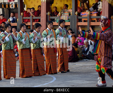 A choir of young ladies is mocked by as masked clown in  the central courtyard  of Trashigang Dzong during Trashigang - Stock Photo