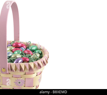 A border of an easter basket filled with chocolate foil eggs Isolated on white - Stock Photo