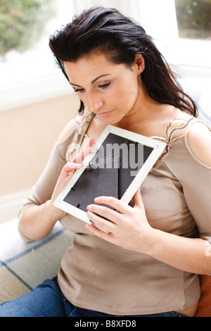 Woman holding photo frame - Stock Photo