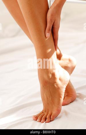 Woman massaging calfs - Stock Photo
