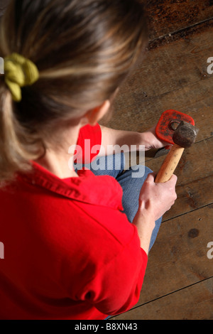 Woman using a hammer and chisel - Stock Photo