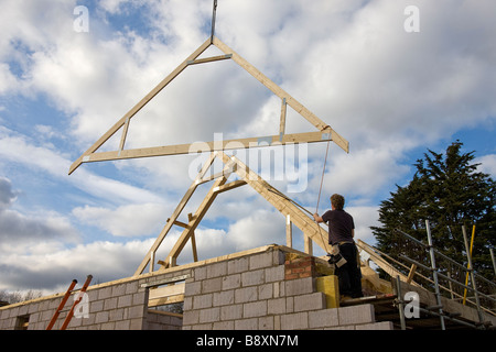 Timber attic roofing truss being lowered into position on roof of new house. - Stock Photo