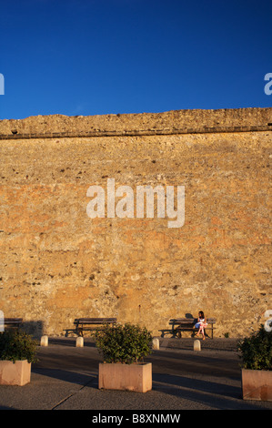 A young woman girl sits at the stone wall in Sardinia's port town of alghero as the sun sets with a deep blue sky - Stock Photo