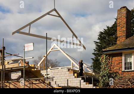 Timber attic roofing truss being hoisted into position on roof of new house. - Stock Photo