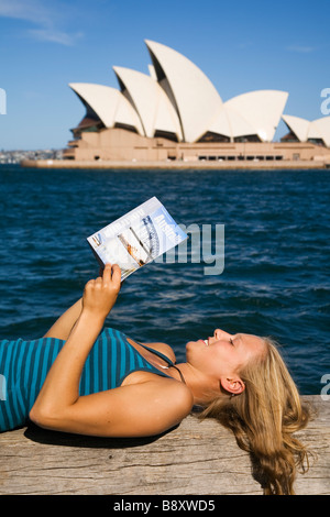 A backpacker reads her guidebook on Sydny harbour with the Opera House in the background.  Sydney, New South Wales, - Stock Photo