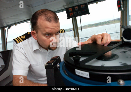 An officer of the Royal Fleet Auxiliary uses a sighting compass on the bridge of the RFA Wave Ruler - Stock Photo