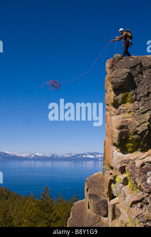 Mountaineer throwing a climbing rope off a cliff, Lake Tahoe, Nevada, USA - Stock Photo